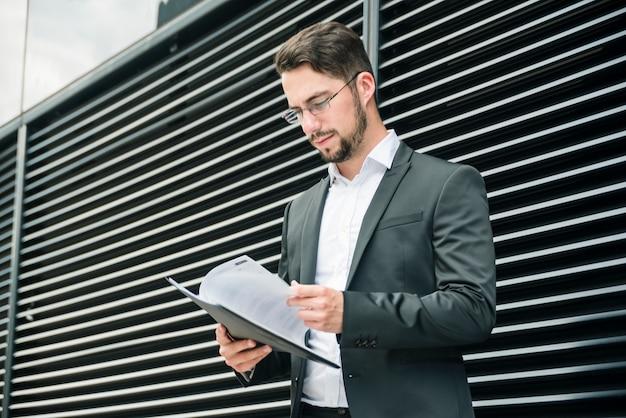 Gros plan, jeune, homme affaires, debout, devant, mur, lecture documents