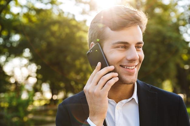 Gros plan d'un jeune homme d'affaires souriant marchant à l'extérieur, parlant au téléphone mobile