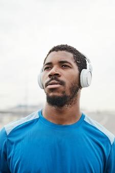 Gros plan d'un jeune homme africain dans des écouteurs sans fil en détournant les yeux tout en s'entraînant à l'air frais