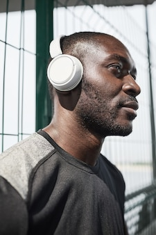Gros plan d'un jeune homme africain dans des écouteurs sans fil en détournant les yeux avec une vue pensive en se tenant debout...