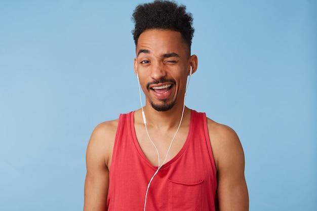 Gros plan d'un jeune homme afro-américain de bonne humeur, porte un maillot rouge, écoute de la musique cool, des clins d'œil et sourit largement.