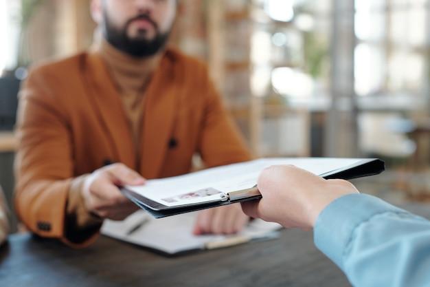 Gros plan sur un jeune homme assis à table et fournissant un curriculum vitae au responsable des ressources humaines lors d'un entretien d'embauche