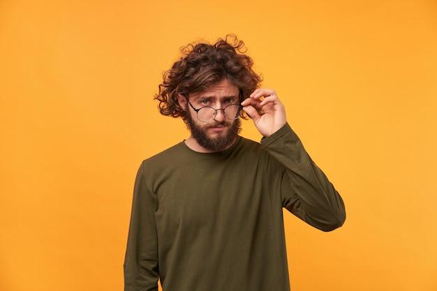 Gros plan d'un jeune homme avec une barbe et des cheveux noirs bouclés, avec intérêt baissé ses lunettes, réfléchissant soigneusement à quelque chose