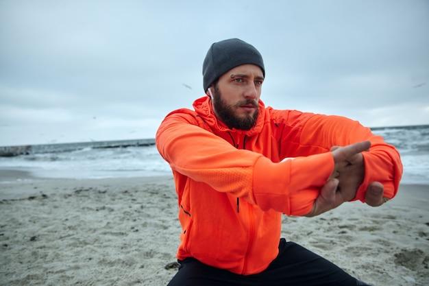 Gros plan d'un jeune homme barbu brune concentré regardant vers l'avant tout en faisant de l'exercice à l'extérieur, fait du sport tous les matins. concept de bien-être de remise en forme masculine