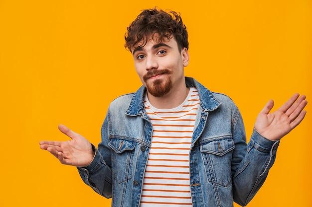 Gros plan d'un jeune homme barbu confus habillé avec désinvolture debout isolé