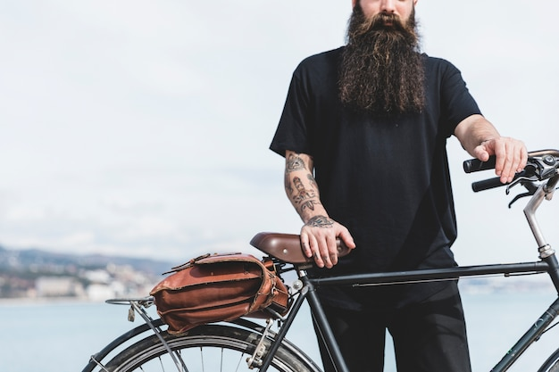 Gros plan, jeune homme barbu, debout, bicyclette