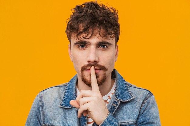 Gros plan d'un jeune homme barbu pensif habillé avec désinvolture debout isolé