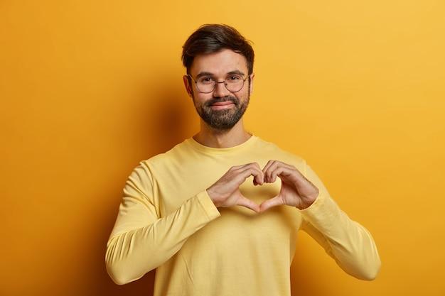 Gros plan sur le jeune homme barbu portant des lunettes isolées