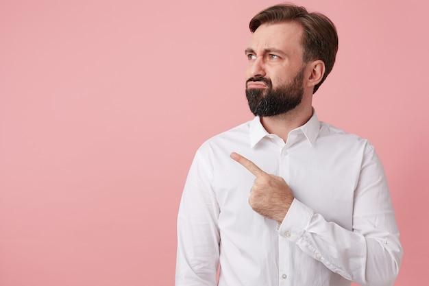 Gros plan d'un jeune homme barbu, qui détourne les yeux avec dégoût, attire votre attention en pointant du doigt sur l'espace de copie à gauche, isolé sur fond rose.