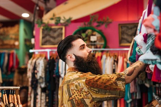 Gros plan d'un jeune homme barbu, regardant les vêtements suspendus sur rail