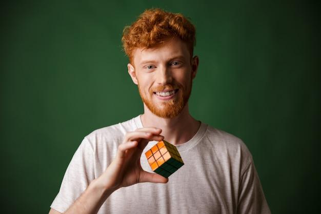 Gros plan d'un jeune homme barbu à tête de lecture souriante, tenant le rubik's cube