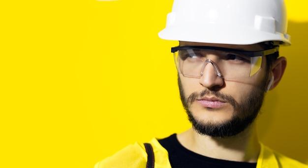 Gros plan jeune homme confiant architecte, ingénieur constructeur, portant un casque de sécurité de construction blanc, des lunettes et une veste jaune sur un mur jaune avec espace de copie.