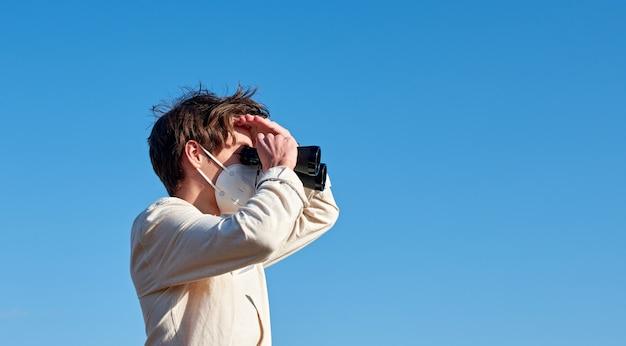 Un gros plan d'un jeune homme dans une chemise blanche à la recherche à travers des jumelles tout en bloquant le soleil d'une main sur l'espace bleu