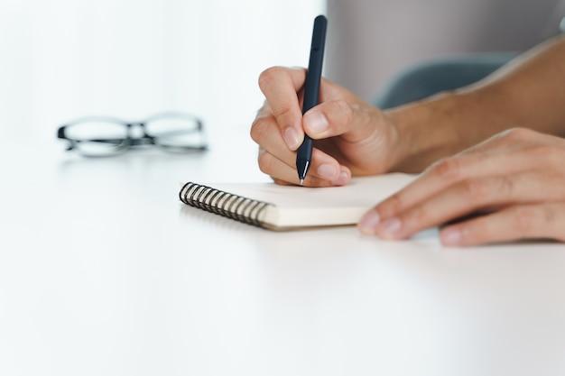 Gros plan d'un jeune homme dans des mains en tissu décontracté écrivant sur le bloc-notes, bloc-notes à l'aide d'un stylo à bille sur la table.
