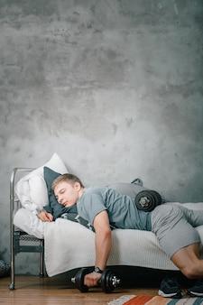 Gros plan, de, a, jeune homme, dans, a, uniforme sport, est, repos, dormir, sur, a, lit, à, a, haltère