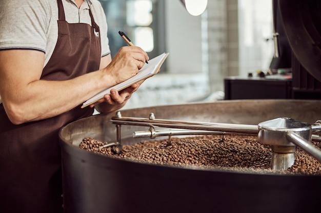 Gros plan jeune homme écrivant sur le presse-papiers en se tenant debout près du plateau de refroidissement avec des grains de café torréfiés