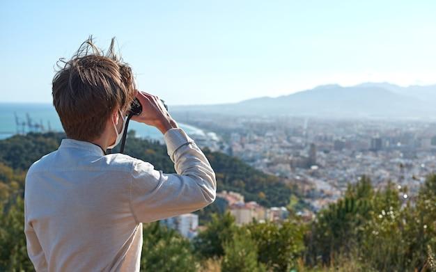 Un gros plan d'un jeune homme d'espagne dans une chemise blanche portant un masque en observant la ville côtière à travers des jumelles