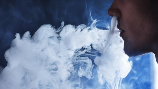 Gros plan d'un jeune homme exhalant un nuage de vapeur ou de fumée à l'aide d'une cigarette électronique. vapage mécanique mod