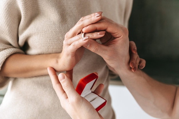 Gros plan d'un jeune homme faisant une proposition à sa petite amie avec une bague dans une boîte à la maison