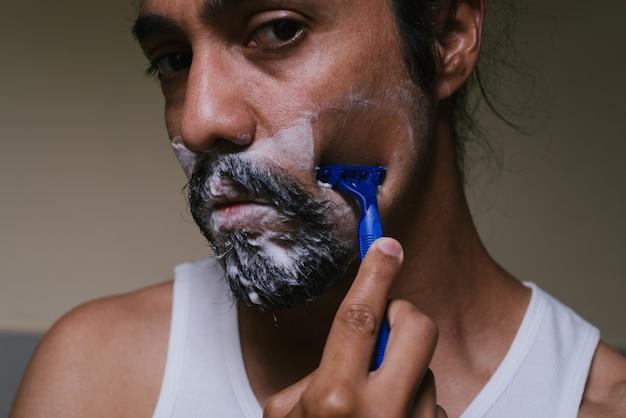 Gros plan d'un jeune homme latino qui rase sa barbe en regardant la caméra
