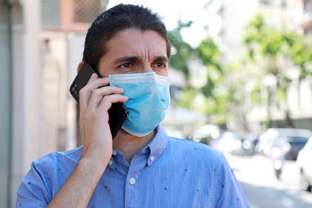 Gros plan jeune homme avec masque chirurgical appelant avec téléphone mobile dans la rue de la ville