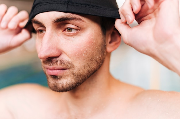 Gros plan, jeune homme, mettre, bonnet de natation