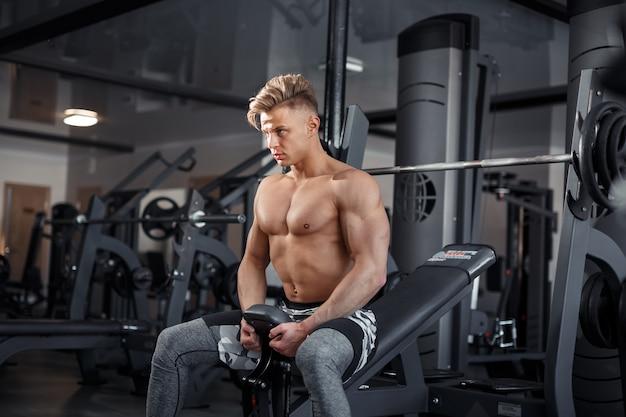 Gros plan d'un jeune homme musclé soulevant des poids dans une salle de sport sur fond sombre. photo de haute qualité