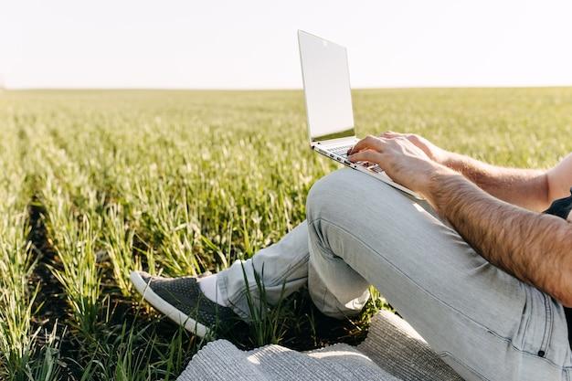 Gros plan d'un jeune homme avec un ordinateur portable travaillant, assis dans un champ avec de l'herbe verte fraîche.