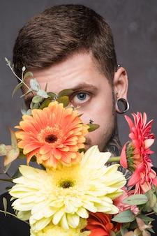 Gros plan d'un jeune homme percé furtivement du bouquet de gerbera