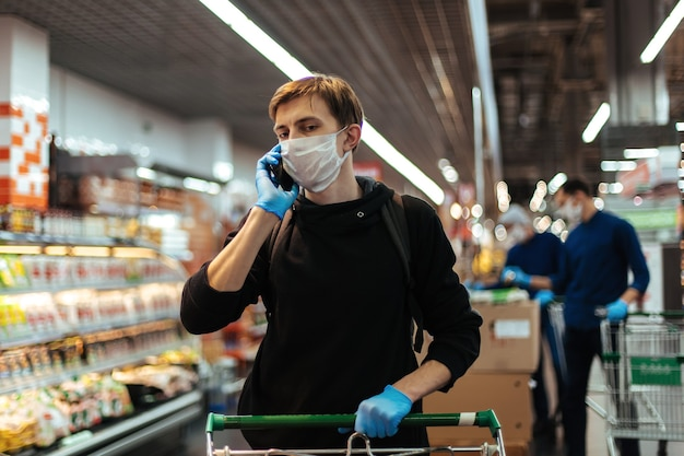 Gros plan sur un jeune homme portant un masque de protection parlant sur son smartphone