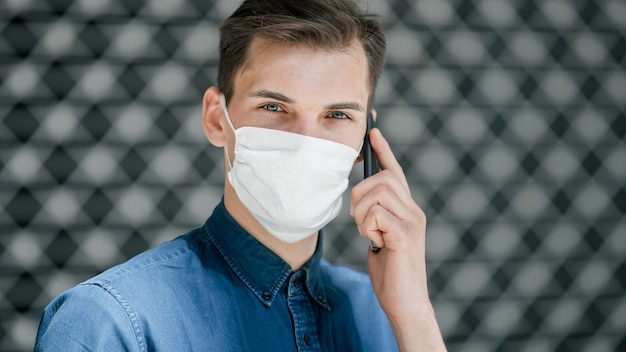 Gros plan sur un jeune homme portant un masque de protection qui vous regarde