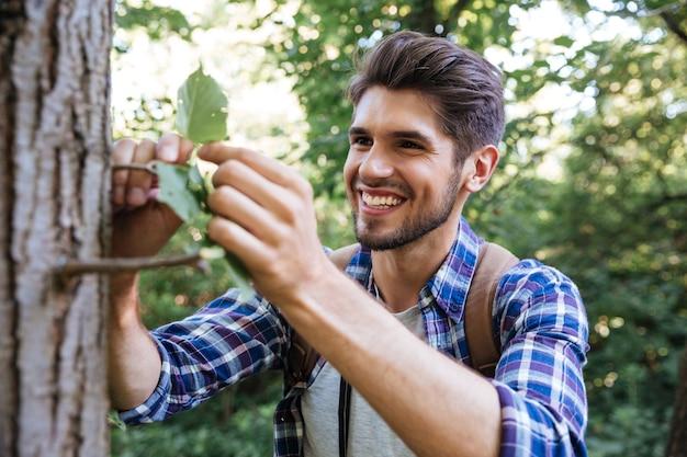 Gros plan jeune homme près de l'arbre