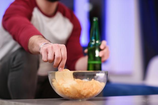 Gros plan d'un jeune homme de race blanche prenant une croustille de pomme de terre dans un bol placé sur une table à côté de différentes autres collations et un verre avec une boisson rouge