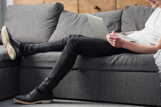 Gros plan, de, a, jeune homme, s'asseoir sofa, regarder, ordinateur portable