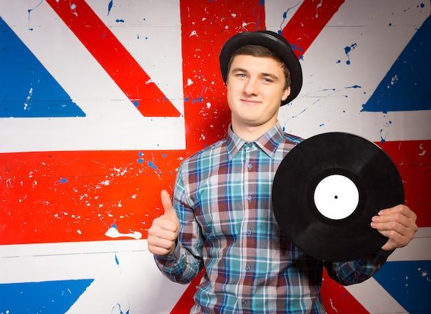 Gros plan sur un jeune homme souriant en chemise à manches longues à carreaux et chapeau tenant un disque vinyle montrant les pouces vers le haut tout en regardant la caméra. capturé sur fond d'impression de drapeau britannique.