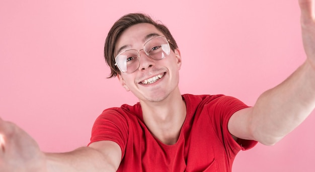Gros plan jeune homme souriant dans des vêtements décontractés posant isolé sur fond de mur rose, portrait en studio. concept de mode de vie des émotions sincères. copiez l'espace pour la copie.