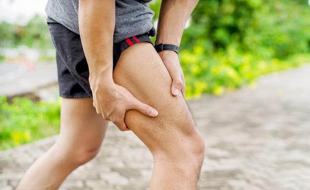 Gros plan d'un jeune homme sportif asiatique a des douleurs aux muscles et aux articulations pendant l'exercice en plein air, sur l'entraînement ou la course et le concept d'injuty de sport