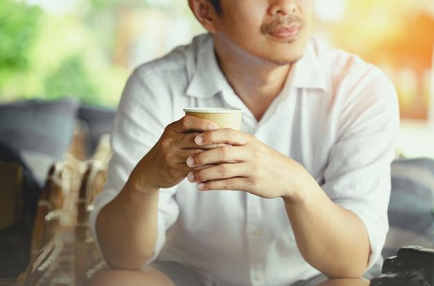 Gros plan d'un jeune homme tenant un café à emporter tôt le matin à la maison, lumière du soleil, mur flou.