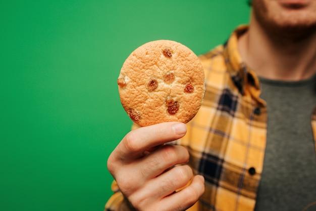 Gros plan, jeune homme, tient, cookie