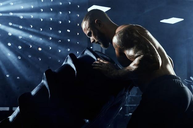 Gros plan d'un jeune homme torse nu en forme de mouvement de roue géante dans une salle de sport.