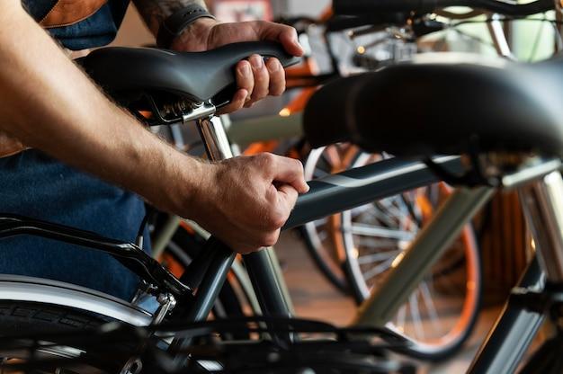Gros plan sur un jeune homme travaillant sur un vélo
