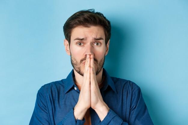 Gros plan d'un jeune homme triste implorant, implorant de l'aide et dire s'il vous plaît, debout sur fond bleu.