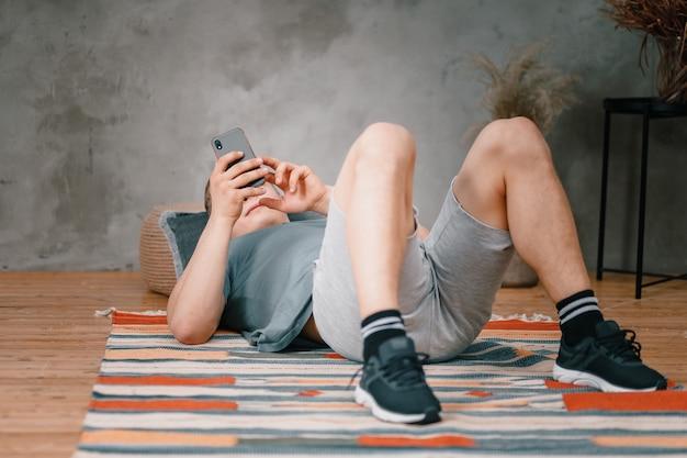 Gros plan d'un jeune homme en uniforme de sport repose sur le sol à la maison, regardant le téléphone sur un réseau social. étudiant flânant et retardant le travail et les études