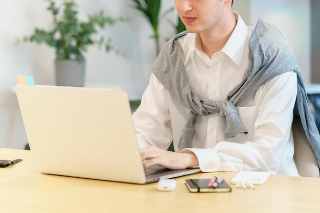 Gros plan d'un jeune homme utilisant un ordinateur portable dans un espace décontracté
