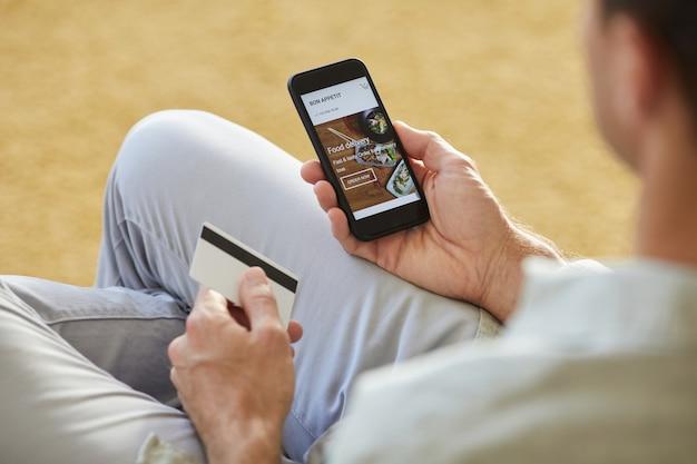 Gros plan, de, jeune homme, utilisation, téléphone portable, pour, commander, livraison nourriture, il, payer, par, carte crédit