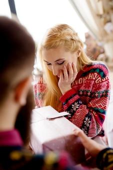 Gros plan de jeune jolie fille hipster dans un pull pour obtenir une boîte-cadeau de son petit ami barbu prudent à la maison pour les vacances de noël.