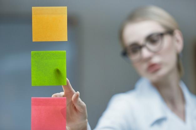 Gros plan sur un jeune médecin collant des autocollants colorés sur un verre transparent