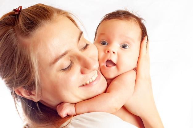 Gros plan d'une jeune mère attentionnée essuie une petite fille mignonne d'un demi-an après le bain sur un fond blanc. place pour la publicité des produits pour bébés. copyspace