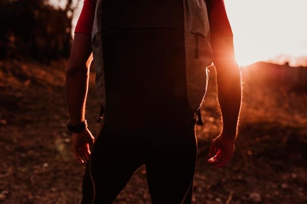 Gros plan d'un jeune randonneur homme à la montagne au coucher du soleil. concept sportif