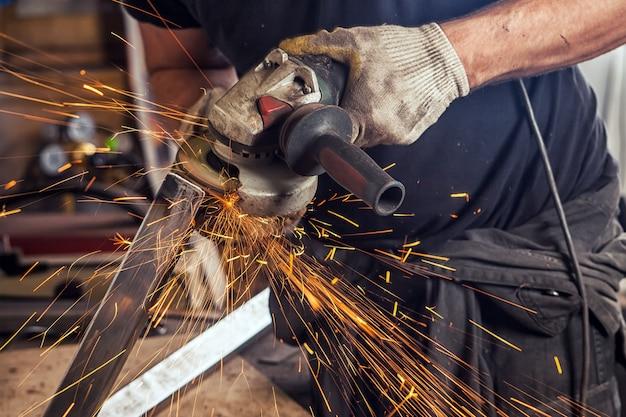 Gros plan un jeune soudeur broie du métal avec une meuleuse d'angle dans l'atelier